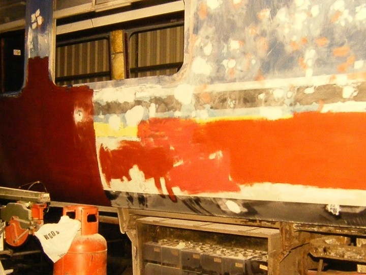 Master painter Joe Galbraith has the body side well rubbed down in preparation for a coat of primer.