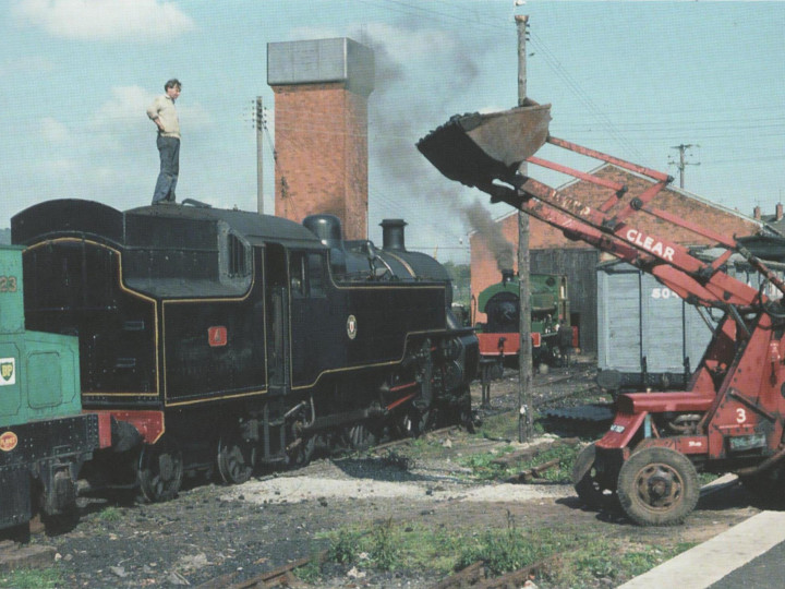 6/8/1977: An out-of-steam No 4 has been positioned by the Planet diesel and Ken Pullin is directing the shovel with its ton load of coal. In the background No.3 'R.H. Smyth' is being steamed for train rides duty. (C.P. Friel)